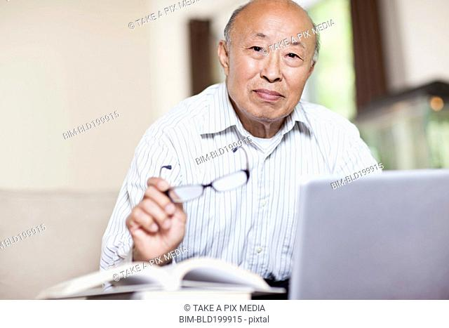 Chinese man with book and laptop