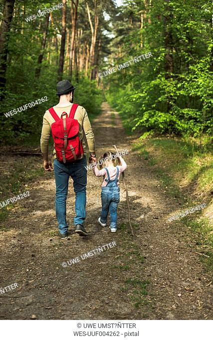 Father and daughter hiking in forest