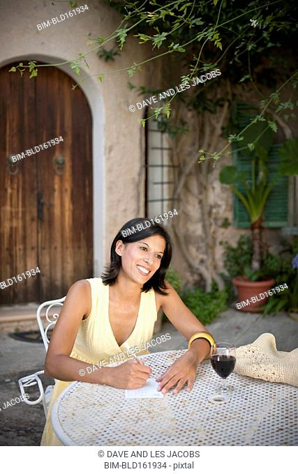 Hispanic woman writing in backyard