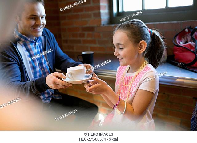 Father and daughter with cappuccino in coffee shop