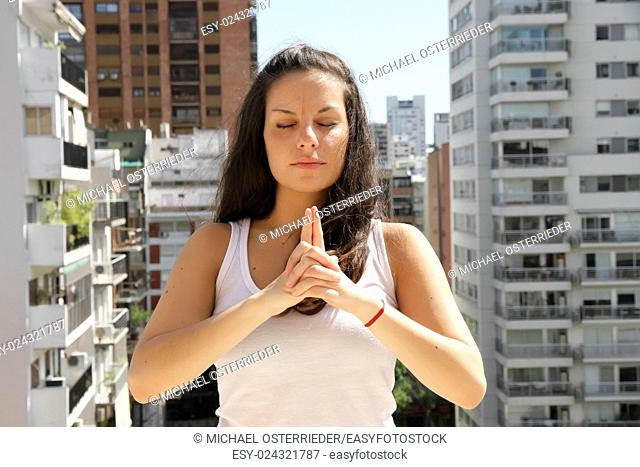 A young adult woman practicing Yoga in an urban environment