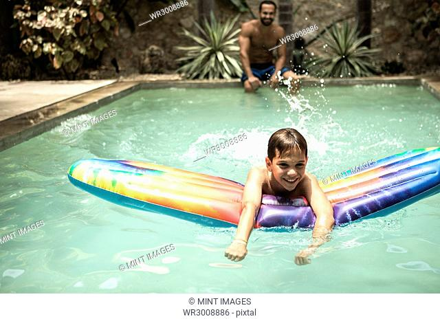 A boy floating on a pool raft in a swimming pool