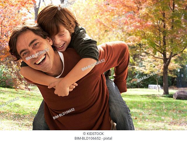 Caucasian father giving son a piggyback ride