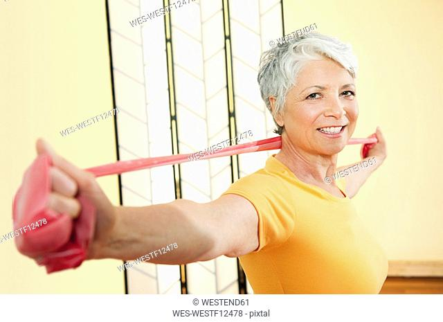 Senior woman exercising with elastic band, smiling, portrait