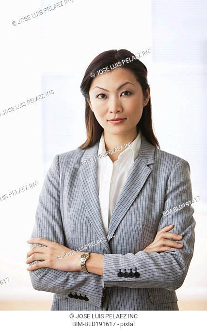 Confident Chinese businesswoman standing with arms crossed