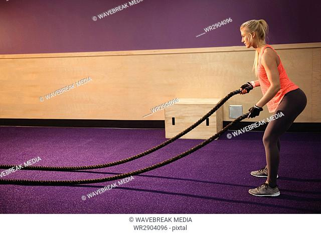 Fit woman doing battle rope exercise