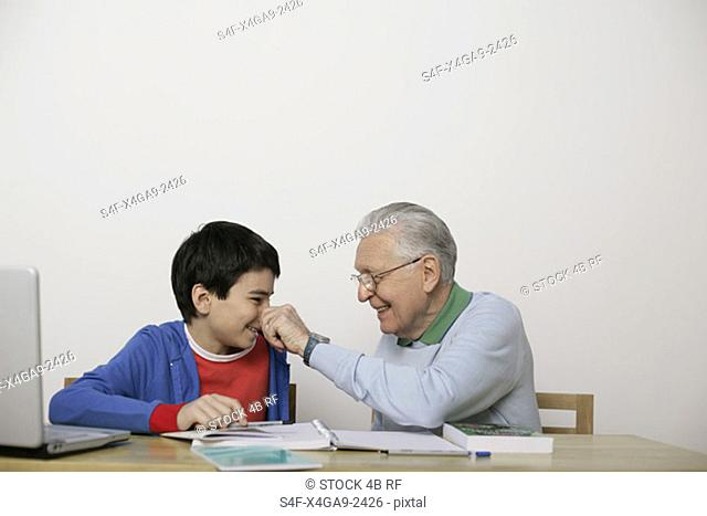 Grandfather pinching boy's nose, fully-released