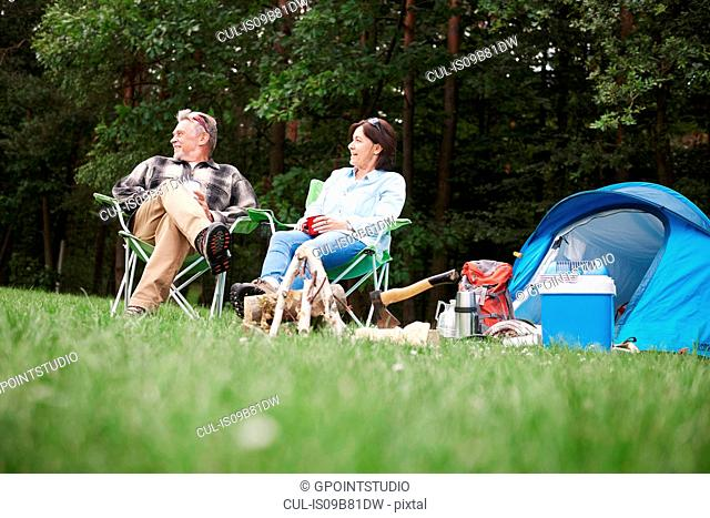 Mature couple sitting in camping chairs beside tent, low angle view