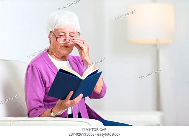 Portrait of a senior woman at home - Looking happy, looking at the camera, smiling while sitting on the sofa in her living room and reading a good book