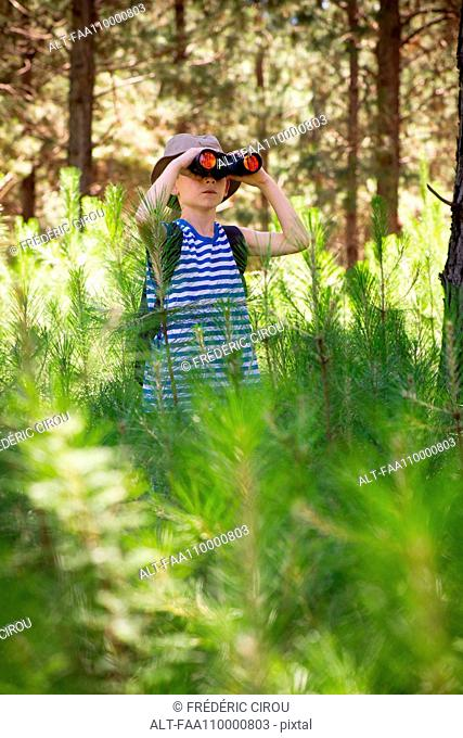 Boy using binoculars in woods