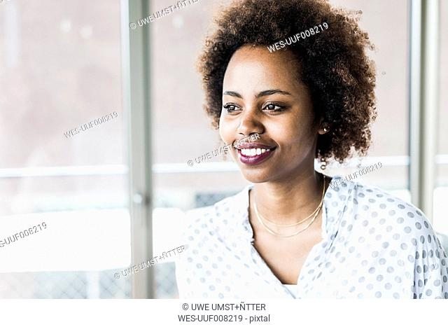 Portrait of smiling businesswoman looking through window