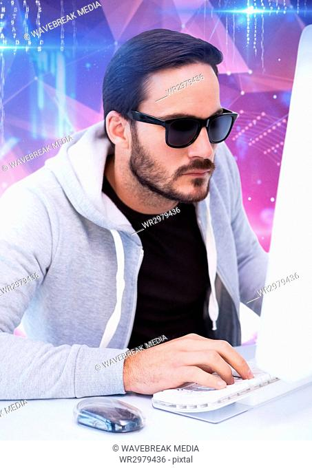 hacker with sunglasses typing on a keyboard in front of digital background