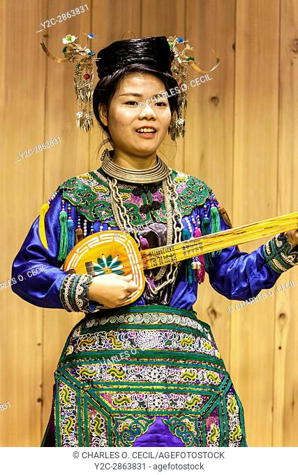 Zhaoxing, Guizhou, China. Young Woman of the Dong Ethnic Minority Playing a Five-stringed Lute (pipa)