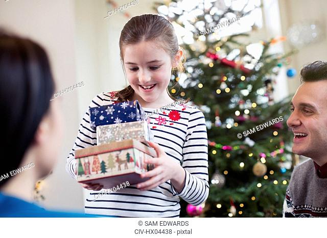 Girl gathering gifts in front of Christmas tree