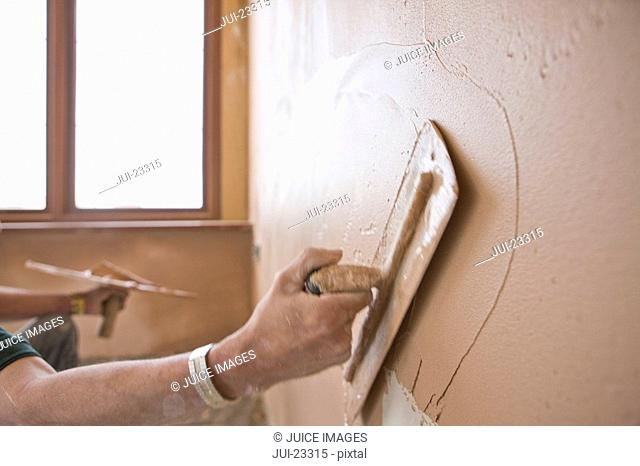Man plastering wall with trowel