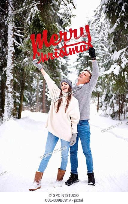 Young couple with Merry Christmas words in snow
