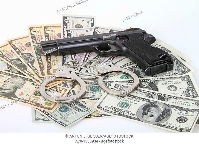 Symbolic , dollar bank notes , handcuffs and gun