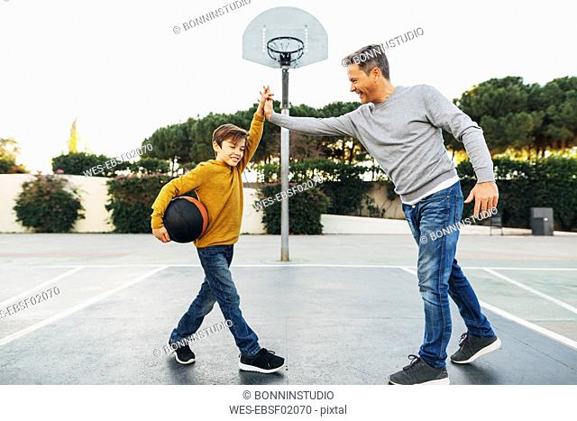 Father and son high fiving on basketball outdoor court