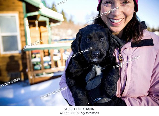 Young Woman Holds Her Bernese Mountain Dog Puppy Outdoors During Winter With A Cabin In The Background Near Homer, Alaska