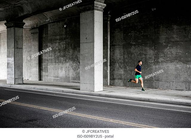 Young male runner running through underpass