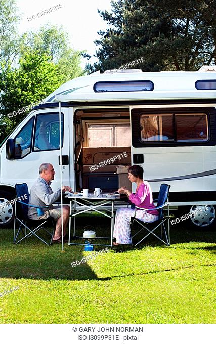 Couple eating breakfast outside campervan