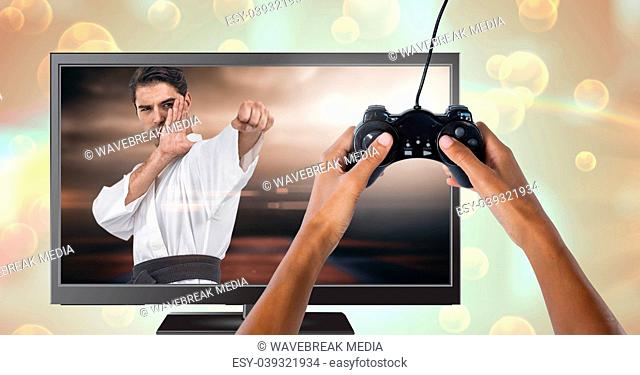 Hands holding gaming controller with martial arts fighter player on television