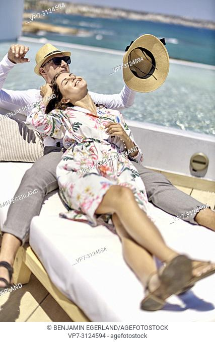 playful couple relaxing on sunbeds, holiday, love, togetherness