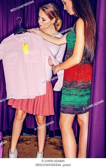 Two young women in fitting room with a blouse