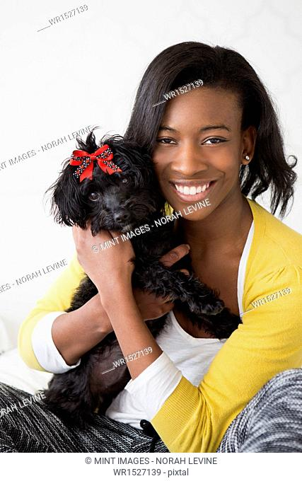 A young girl smiling, holding her small black pet dog
