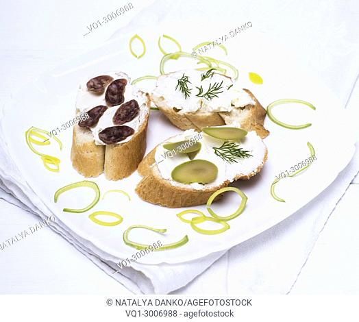 sandwiches with creamy white cheese, sausage, olives and dill on a white plate, wooden white table