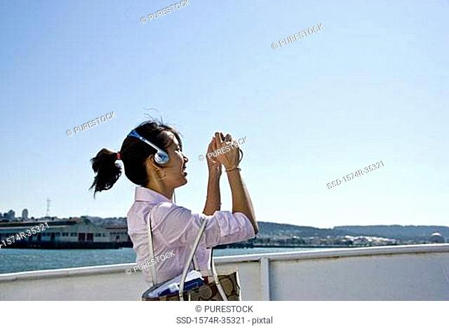 Side profile of a young woman taking a picture with a digital camera, San Francisco, California, USA