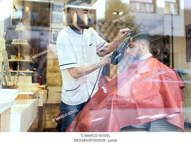 Barber blow-drying hair of a customer in a barber shop