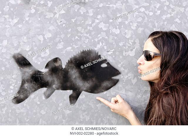 Woman is kissing a black graffiti fish on a gray wall