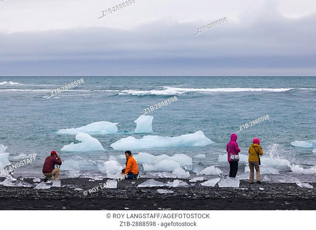 Tourists looking at the ice chunks floating out of the Jokulsarlon glacier lagoon in Iceland