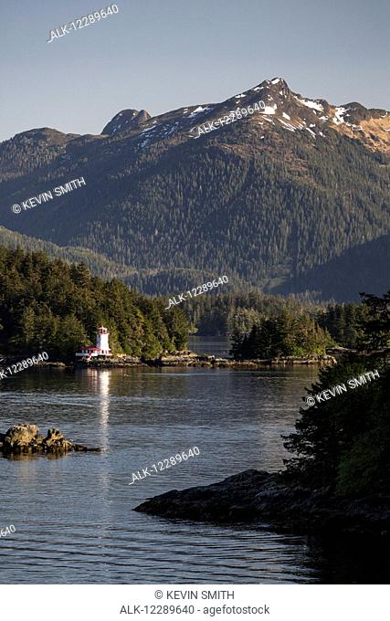 Small islands populated by Sitka spruce trees, a lighthouse in the background; Sitka, Alaska, United States of America