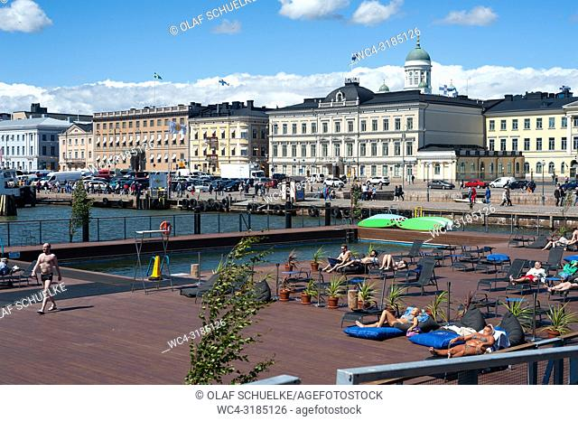 Helsinki, Finland, Europe - Visitors sunbathe on the Allas Sea Pool terrace with a view of the harbour and the central market square