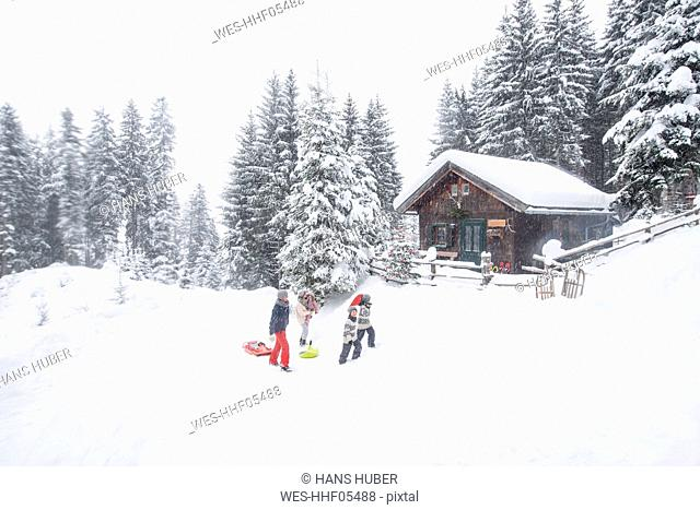 Austria, Altenmarkt-Zauchensee, family with sledges at wooden house at Christmas time