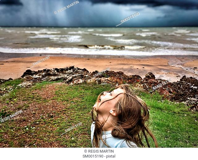 little girl playing along a beach in front of an incoming storm