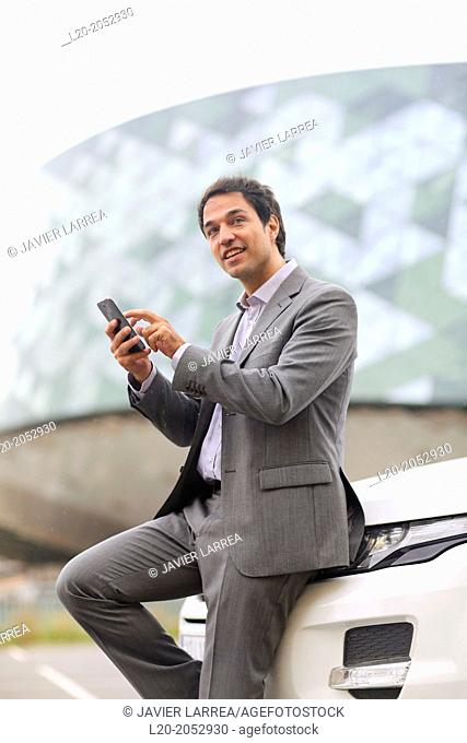 Business man with smartphone in parking business center. San Sebastian Technology Park. Donostia. Gipuzkoa. Basque Country. Spain