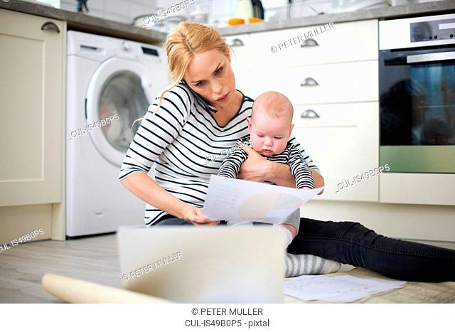 Woman holding baby son in arms, whilst looking through work on kitchen floor, speaking on smartphone and looking at laptop in front of her
