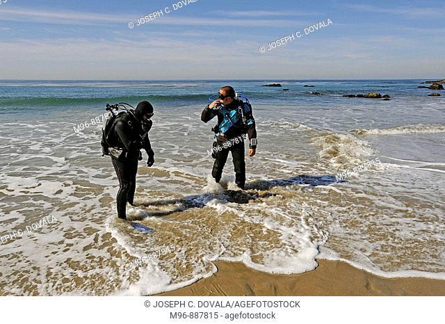 Scuba divers enter water backwards, Malibu, California, USA
