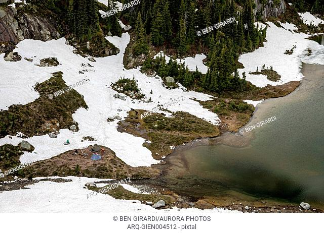 Three people set up camp at Semaphore Lake, an alpine lake and meadow area with relatively easy access from a logging road making it a popular backpacking...