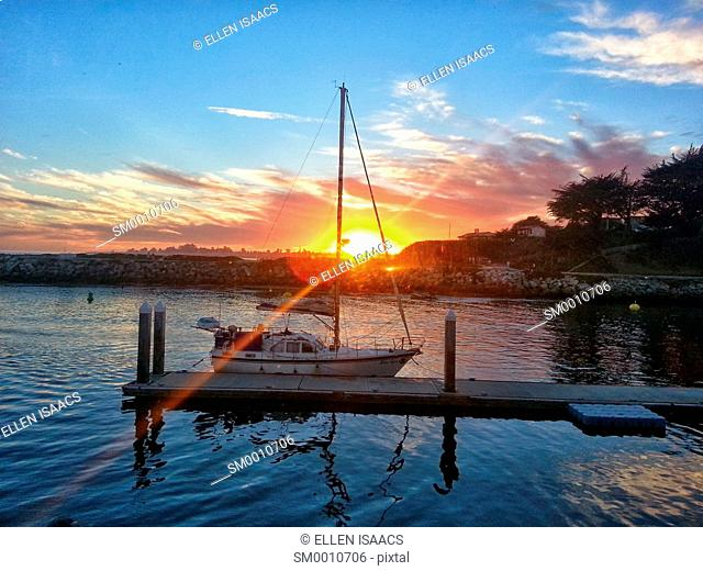 Flare of sun setting over a harbor with a boat docked by a pier in Santa Cruz, California