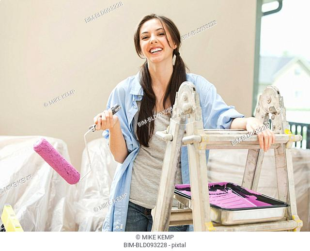 Caucasian woman holding paint roller