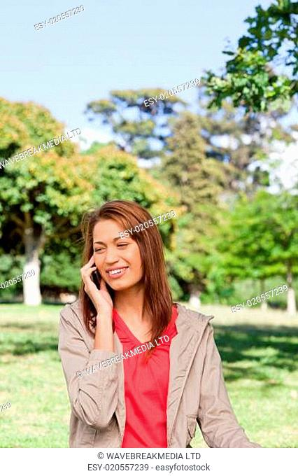 Woman smiling while making a phone call in and area surrounded by trees