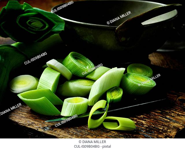 Chopped raw leeks on rustic wooden chopping board