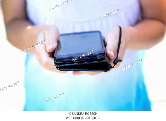 Girl's hands holding smartphone, close-up