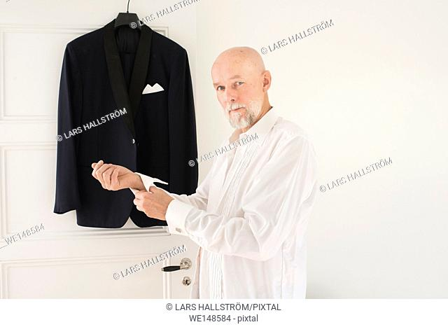 Old man putting on clothes at home, dinner jacket hanging in the background. Lifestyle moment of active retirement