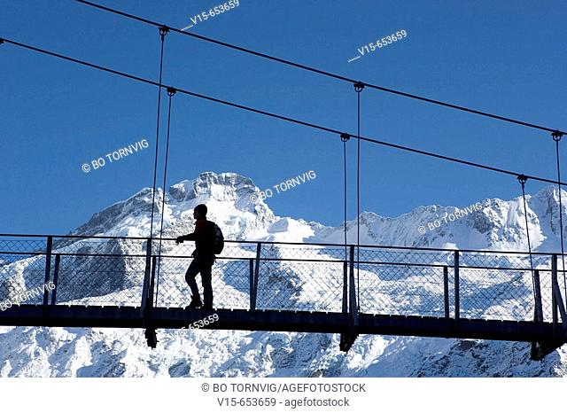 Hiker at swingbridge in snow covered Mountains