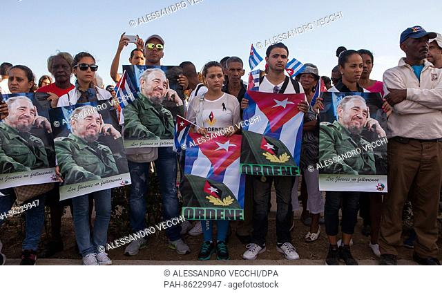 Santiago de Cuba, Cuba - 04.12.2016. Youngsters are holding posters on one of the roads to Santa Ifigenia's cemetery while creating a barrier to the cemetery...